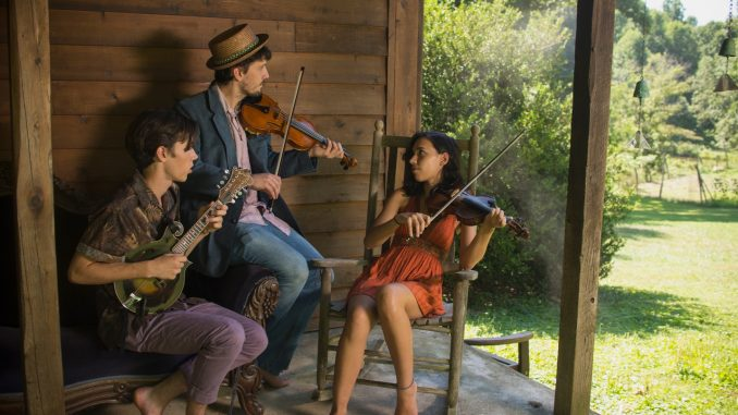Group of three people playing musical instruments in a wooden house